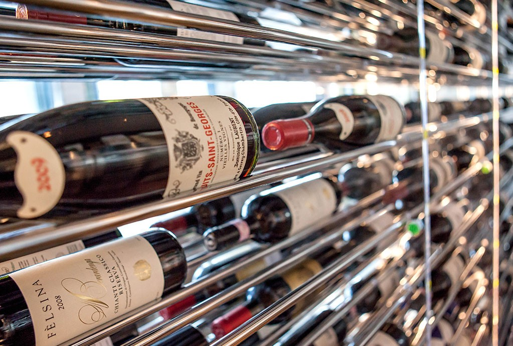 Contemporary wall-mounted wine holding racks behind an elegant bar