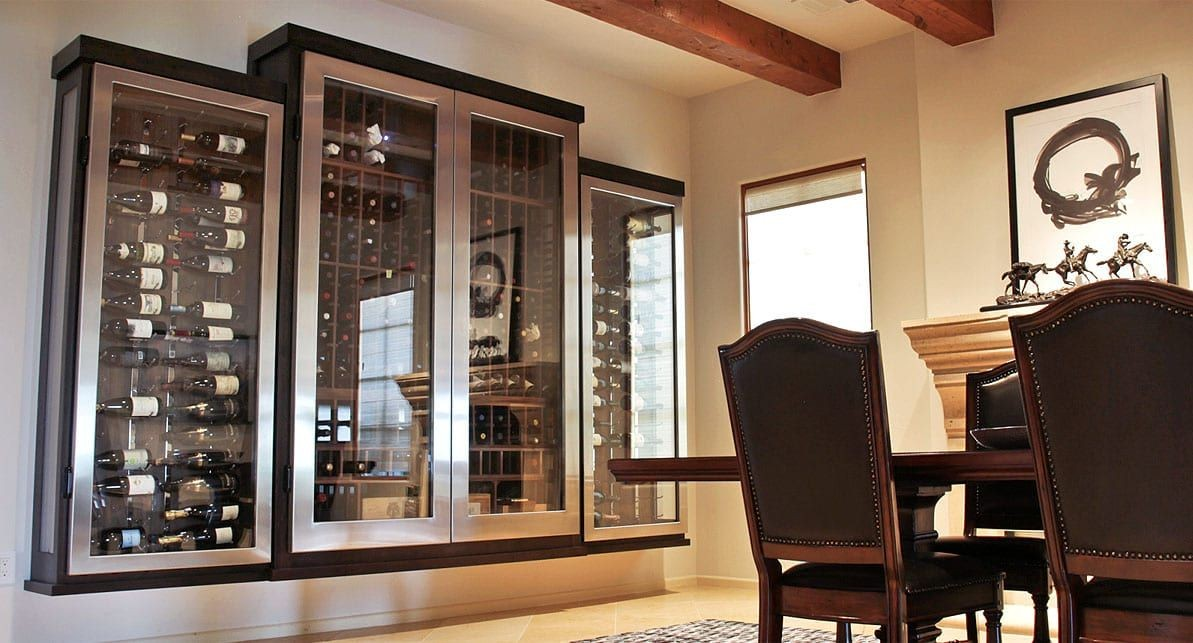 Dramatic stainless steel edged custom glass enclosed wine cabinet.