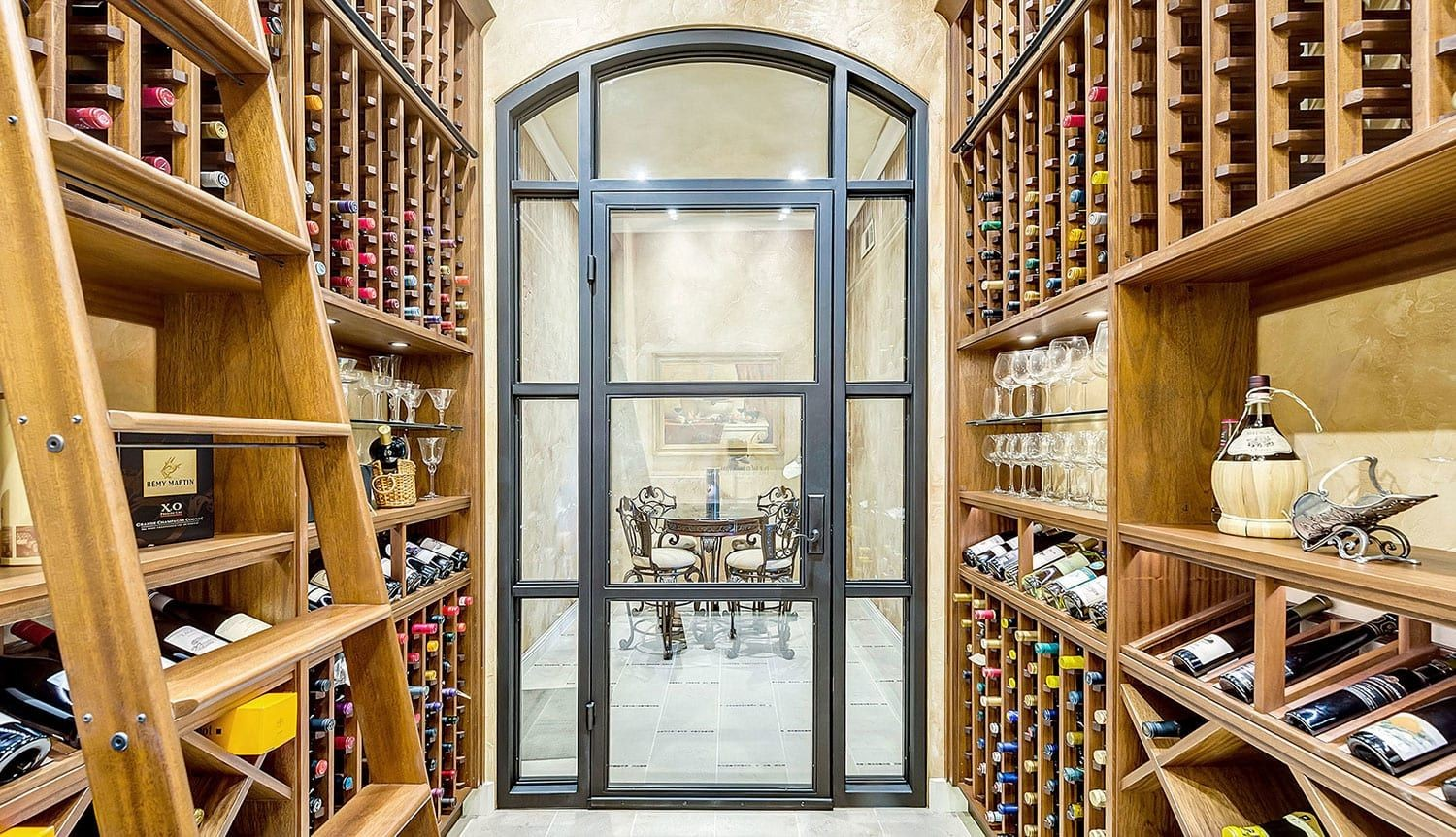 Stunning wood wine cellar custom made for a Texas home with a dramatic arched window and ladder.